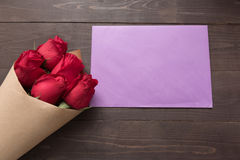 Красные розы цветут с карточкой на деревянной предпосылке Стоковая Фотография RF