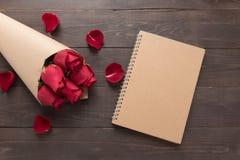 Красные розы цветут с тетрадью на деревянной предпосылке Стоковое Изображение RF