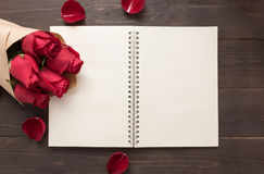 Красные розы цветут с тетрадью на деревянной предпосылке Стоковые Фото