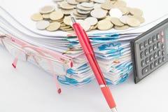 Красные ручка и куча обработки документов имеют золотые монетки стога Стоковое фото RF