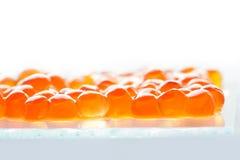 Красные рыбы семг икры на стеклянной пластинке и белой предпосылке малая глубина взгляда макроса поля стоковое изображение