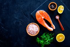 Красные рыбы с специями Salmon стейк на разделочной доске около соли моря, перца, кусков лимона, растительности на черной предпос Стоковые Фотографии RF