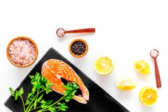 Красные рыбы с специями Salmon стейк на разделочной доске около соли моря, перца, кусков лимона, растительности на белой предпосы Стоковое Изображение RF