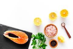 Красные рыбы с специями Salmon стейк на разделочной доске около соли моря, перца, кусков лимона, растительности на белой предпосы Стоковые Фото