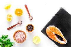 Красные рыбы с специями Salmon стейк на разделочной доске около соли моря, перца, кусков лимона, растительности на белой предпосы Стоковые Фотографии RF
