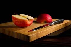 Красные свежие яблоки, прерванные вверх на старой доске Стоковое Фото