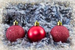Красные сверкная глобусы рождества на концепции предпосылки зимы Стоковые Изображения