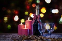 Красные свечи и бутылка шампанского над снегом стоковое фото