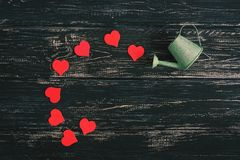 Красные сердца льют из моча чонсервной банкы, старой черной деревянной предпосылки Стоковые Фотографии RF