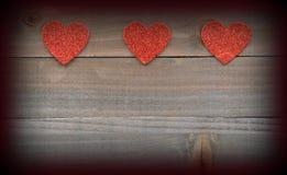Красные сердца на деревянной предпосылке с виньеткой Стоковое фото RF