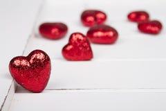 Красные сердца яркого блеска на белой деревянной предпосылке Стоковые Фото