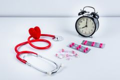 Красные сердце и стетоскоп, будильник, лекарства, пилюльки на таблице Стоковая Фотография
