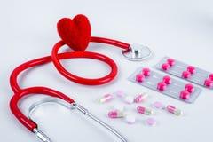 Красные сердце и стетоскоп, лекарства, пилюльки на таблице Стоковые Фото