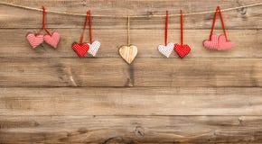 Красные сердца вися на деревянной предпосылке красный цвет поднял Стоковое Фото