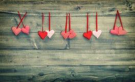 Красные сердца вися на деревянной предпосылке красный цвет поднял Стоковое Изображение RF