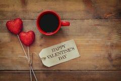 Красные сердца и чашка кофе на деревянной предпосылке Стоковые Изображения