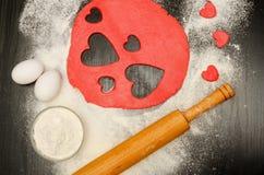 Красные сердца режа тесто с яичками, мукой и вращающей осью на черной таблице Стоковое Фото