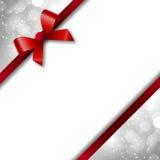 Красные смычок и лента на праздничном bokeh предпосылки Стоковое Изображение