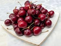 Красные сочные вишни на белой плите Стоковые Изображения
