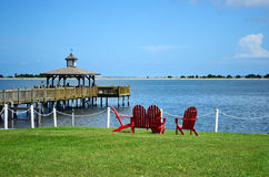 Красные стулья над смотреть водный путь и частную пристань Стоковое Фото