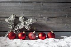 Красные сферы рождества на куче снега против деревянной стены Стоковая Фотография