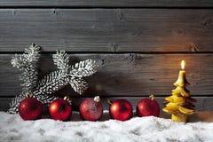 Красные сферы рождества на куче снега против деревянной стены Стоковое фото RF