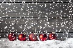 Красные сферы рождества на куче снега против деревянной стены Стоковые Фотографии RF