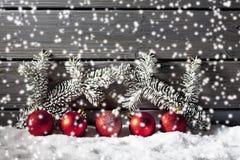 Красные сферы рождества на куче снега против деревянной стены Стоковое Изображение RF