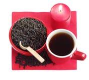 Красные тарелки с черным чаем и горящей свечкой Стоковые Изображения RF