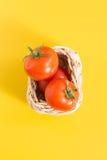 Красные томаты вишни в плетеной корзине, на желтой предпосылке Стоковое фото RF