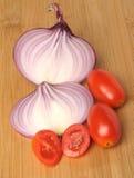 красные томаты вишни и отрезанный красный лук на бамбуковой доске куска Стоковые Изображения RF