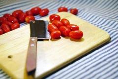 Красные томаты и нож вишни Стоковые Фотографии RF