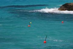 Красные томбуи в голубом море около Кипра плавают вдоль побережья Стоковое Изображение RF