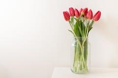 Красные тюльпаны в высокорослом стеклянном опарнике Стоковое Изображение RF