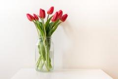 Красные тюльпаны в стеклянном опарнике на таблице Стоковая Фотография RF