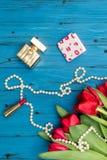 Красные тюльпаны на голубой деревянной доске Стоковое Фото