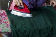 Красные утюги, утюжа утюги, домохозяйки делают выглаживатель тканей Стоковые Изображения RF