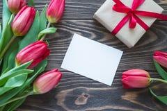 Красные цветки и подарок тюльпана с красными лентой и поздравительной открыткой дальше Стоковое Изображение