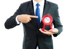 Красные часы держа в руках бизнесмена изолированными Стоковое Фото