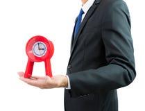 Красные часы держа в руках бизнесмена изолированными Стоковые Фотографии RF