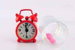 Красные часы и розовая таблетка в стекле дозировки на белой предпосылке Стоковые Фото