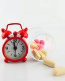 Красные часы и таблетка в стекле на белом backgroud Стоковое Изображение RF