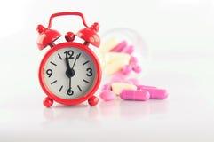 Красные часы и таблетка микстуры Стоковое фото RF