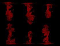 Красные чернила в воде на черноте Стоковое Изображение