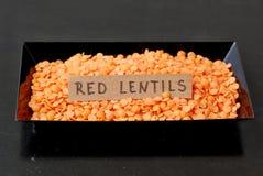 Красные чечевицы в черной плите с ярлыком на черной предпосылке Стоковые Изображения
