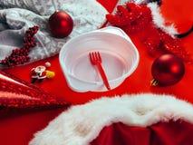 Красные шарики покрывают поздравительную открытку Нового Года предпосылки украшения безделушек белого рождества кардигана шляпы р стоковые фото