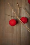 Красные шарики строки на ветви на нейтральной стене Стоковая Фотография