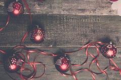 Красные шарик и ленты рождества на деревянной предпосылке invitation new year Рамка Взгляд сверху фото тонизировало Стоковые Фото