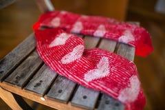Красные шерстяные носки на деревянном стуле Стоковые Изображения RF
