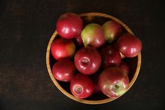Красные яблоки в деревянном шаре на деревянном столе кабанины стоковое изображение